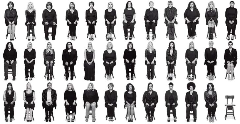 35 women and one empty chair against a white background, seated in 3 rows and facing the camera.