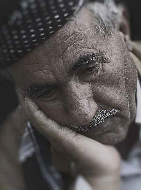 Desaturated close-up of a man holding his head in one hand.