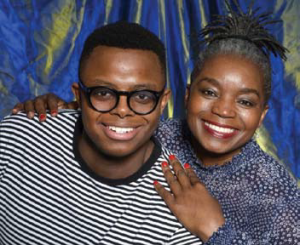 A young man wearing a striped shirt and black glasses next to an older wiman wearing a blue outfit.
