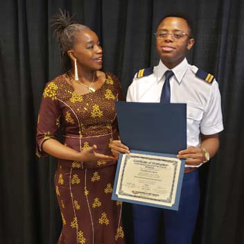 A woman in a dress and a young man in a pilots uniform holding a degree.