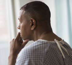 Black man wearing hospital gown indoors, looking out window.