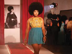 A model with an afro walking down the runway.