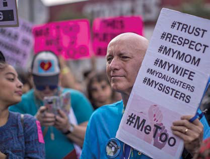 Man at a rally holding a sign in support of #MeToo