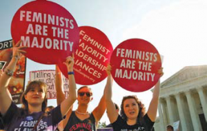 "Three people at an event holding circular signs. One reads ""Feminists are the majority""."