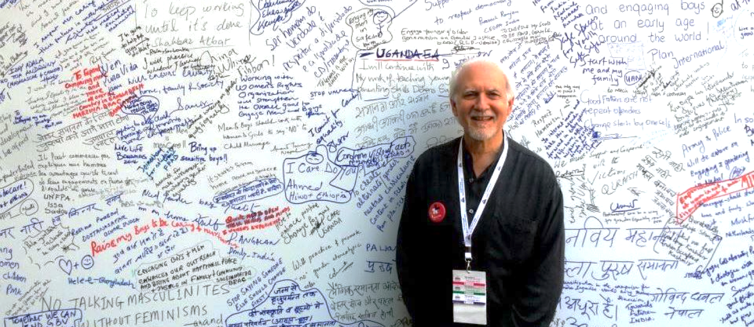 Editor Rob Okun in front of a wall at the Delhi Call to Action. Attendees have handwritten messages on the wall.