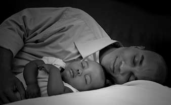grayscale image of a person sleeping while cradling an infant