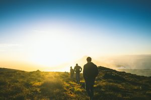 Three men in a single file line on a hill. They are walking away from the camera into a sunset.