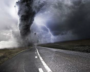 greyscale photo of tornado and lightning above road