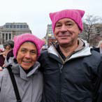 "Two people at a rally wearing pink ""pussy hats"""